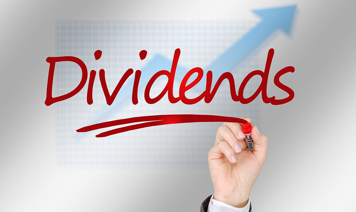 The word DIVIDENDS written in red marker on top of a blue growth line graph arrow which shows an upward trend